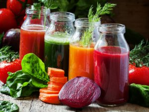 Four kind of vegetable juices: red, burgundy, orange, green, in small glass bottles, fresh vegetables and herbs, vintage wooden background, selective focus